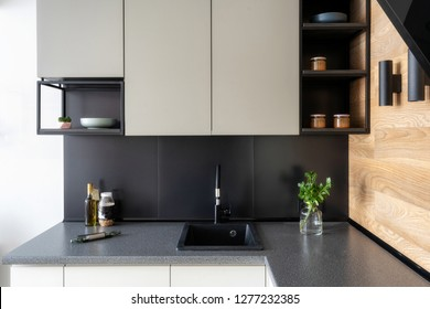 Elegance interior concept. Photo of black and white modern kitchen furniture with shelf and different stuff on table