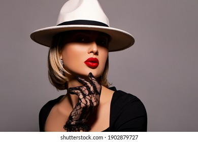 elegance portrait of a young stylish woman in a white hat. makeup - red lips. Fashion model girl posing on gray background studio. Beautiful girl wearing glamorous lace black gloves and dress