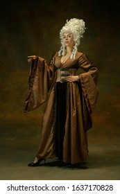 Elegance posing. Portrait of medieval young woman in brown vintage clothing on dark background. Female model as a duchess, royal person. Concept of comparison of eras, modern, fashion, beauty.