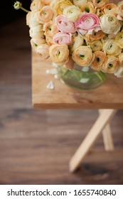 Elegance ranunculus bouquet on wooden table. Beautiful flowers composition in pastel colors: rosy yellow and biege. Perfectly for Birthday Women's and Valentine's Day Anniversary. Copyspace. Top view.