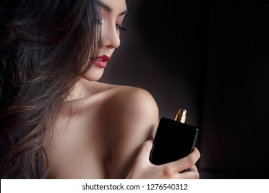 Elegance Sexy Sensual Beautiful Woman Applying Paris, France Luxury Black Bottle fragrance perfume . Young Elegant Girl  Red Lips on dark background.