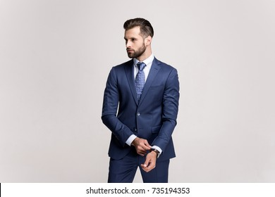 Elegance and success. Handsome young man adjusting his sleeve and looking away while standing against white background.