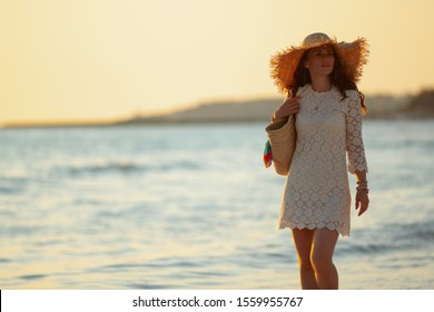 elegant 40 year old woman in white dress and straw hat on the ocean coast at sunset walking.