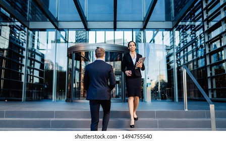 Elegant African American businesswoman with tablet walking on steps with male coworker on background of entrance into contemporary office building
