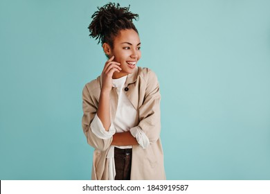 Elegant african american woman posing in beige trench coat. Stylish black young lady isolated on turquoise background.