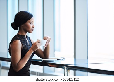 Elegant African American woman thoughtfully looking out the large window while holding her cup of tea in her hands, resting one elbow on the counter maintaining regal posture