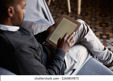 Elegant African black man using tablet on sofa couch in home living room