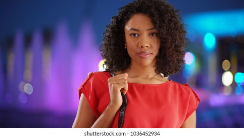Elegant African female youth posing with purse by outdoor fountain at night