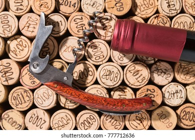 Elegant, already open corkscrew and the bottleneck of a bottle of wine lie on a background of many different vintage corks