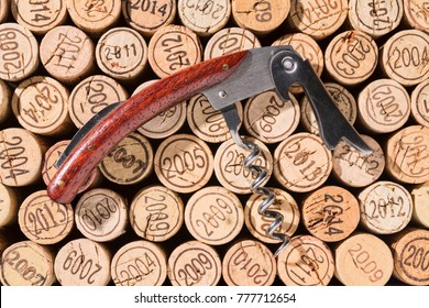 Elegant, already open corkscrew lies on a background of many vintage corks