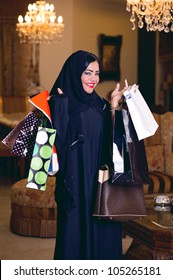 elegant arabian lady with hijab holding shopping bags