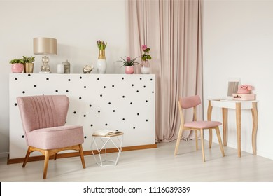 Elegant armchair and an open book by a polka dot wall, wooden vanity table and curtains in a white bedroom interior with dirty pink elements