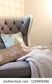 Elegant armchair with throw cushion and chunky knit blanket.
