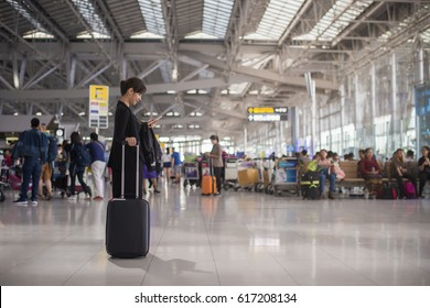 Elegant asian businesswoman checking e-mail on mobile phone with suitcase in airport and airport terminal blurred crowd of travelling people on the background.