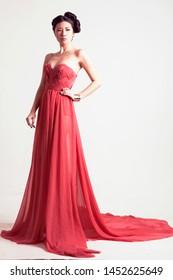 Elegant Asian Woman in Dress Posing. Studio Shoot. White Background.
