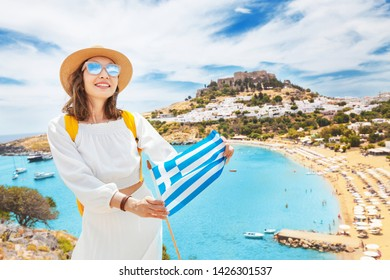 Elegant asian woman in white dress posing with greek flag in front of the famous Lindos town on Rhodes island. Vacation and travel in aa