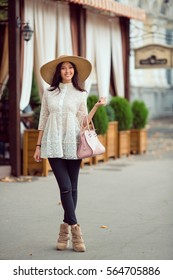 Elegant Asian woman in white dress with hat on the street. Girl standing in full length outside with handbag in modern casual look against blurred city space. Beautiful young mixed race Asian
