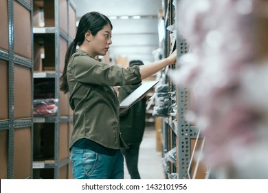 elegant asian woman worker using tablet in warehouse doing stocktaking. blurred view of young girl colleague standing in background in storehouse. female employee concentrated working in stockroom.
