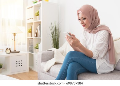 elegant attractive female muslim using mobile smartphone searching online information when she sitting on sofa couch relaxing.