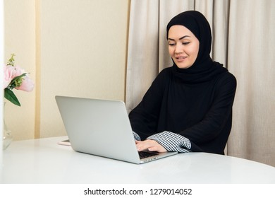 elegant attractive muslim woman using mobile laptop searching online shopping information in living room at home
