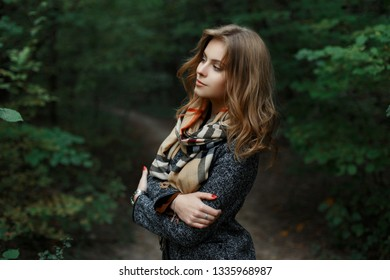Elegant attractive stylish young woman in a luxurious coat in a vintage scarf  stand on a walkway in the park. Wonderful fashionable European girl enjoys nature. Autumn day.