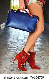 Elegant autumn spring outfit. Fashionable Caucasian boho woman wearing  ankle suede brown high heels with belts, holding leather blue bag