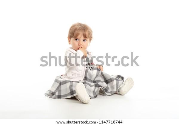 Elegant baby girl 1 year old sitting on the studio floor. White Background.