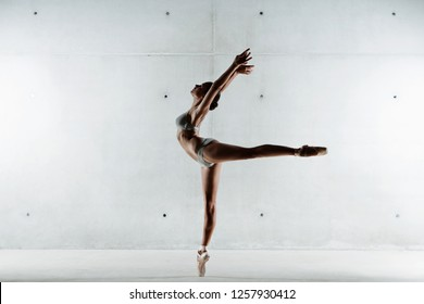 Elegant ballet dancer silhouette lifting leg up with harmony, conceptual power balance, flexibility lightness, stage indoors. Artistic discipline, female stretching shape, beauty body work, energy.