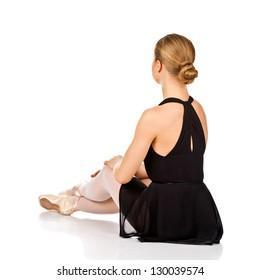 Elegant ballet dancer sitting on the floor. Rear view. Isolated