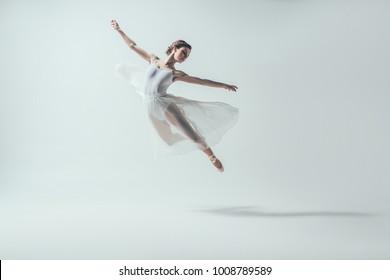 elegant ballet dancer in white dress jumping in studio, isolated on white