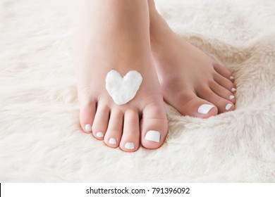 Elegant bare feet. Beautiful groomed woman's feet on the fluffy mat. Cares about clean and soft legs skin in winter time. Heart shape created from cream. Love a body. Healthcare concept.