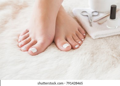 Elegant bare feet. Beautiful groomed woman's feet on the fluffy mat. Scissors, nail files and varnish on the towel. Nail varnishing in white color. Pedicure, manicure beauty salon concept.