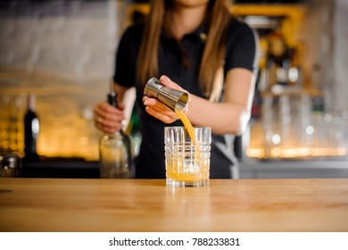 elegant barista in black shirt and with French manicure begins preparing an alcoholic cocktail with juice in a crystal glass