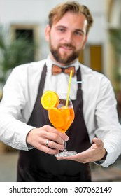 Elegant barman in uniform with butterfly making cocktail with sparkling wine, aperol and orange