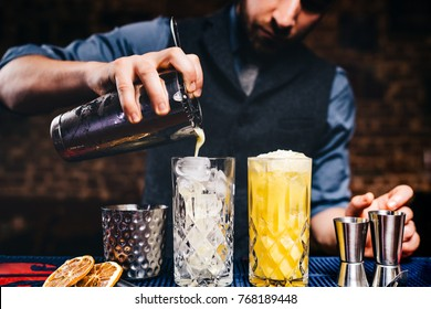 Elegant bartender pouring fresh orange vodka cocktail over ice in crystal glassware
