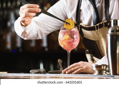 Elegant bartender is preparing pink cocktail holding orange chips at bar counter background.