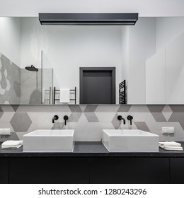 Elegant bathroom in black, white and gray with two washbasins and big mirror