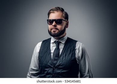 An elegant bearded business man wearing sunglasses and waistcoat on grey background.