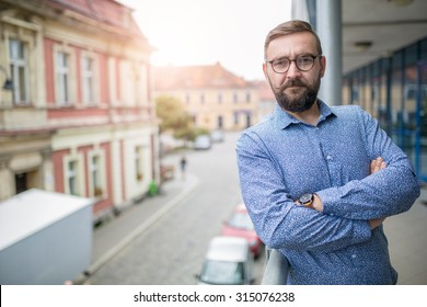 Elegant bearded fashion man standing at balcony with arms crossed and smiling