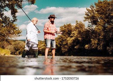 Elegant bearded man and brutal hipster fishing. Hobby sport activity. Master baiter. Father and adult son fishing lakeside. Friends men with fishing rod and net. Retired bearded fisher