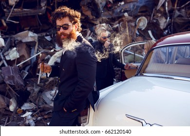 A elegant bearded man in a classic suit with curly reddish hair, black sunglasses, smokes a cigar near vintage car and looks seriously at camera. Bad boy on iron dump background.Horizontal view.