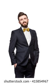 Elegant bearded man in suit, bow tie, hands in the pockets.