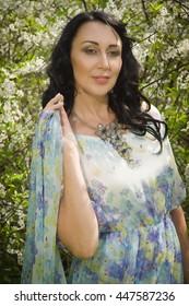 Elegant beautiful adult woman posing in the spring garden