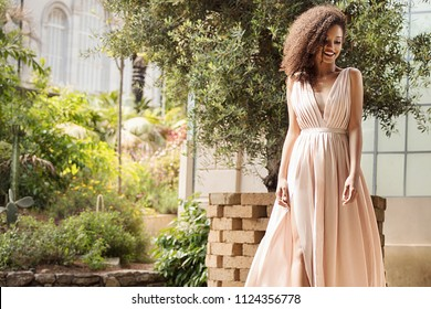 Elegant beautiful african american woman posing in maxi dress outdoor.