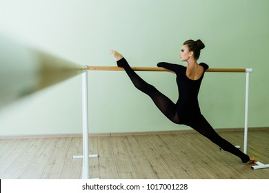 Elegant beautiful ballerina with a perfect body doing stretching twine exercise with barre in dance ballet studio. dancer girl barres. Sexy brunette trains. Dark tights. lifted one leg.