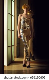 Elegant beautiful blonde woman posing in studio, wearing fashionable dress