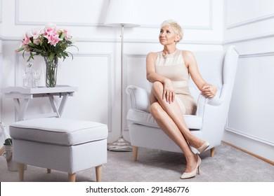 Elegant beautiful blonde woman sitting, relaxing, smiling. Indoor photo.