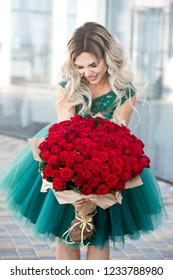 Elegant beautiful blonde woman is wearing green fashion dress in cafe holding with big bouquet of 101 red roses. Birthday.