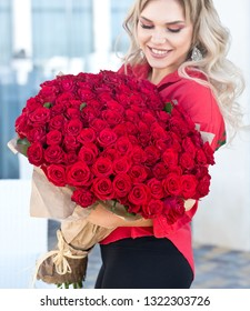 Elegant beautiful blonde woman is wearing green fashion dress in cafe holding with big bouquet of 101 red roses. Birthday. March 8. Valentines day.