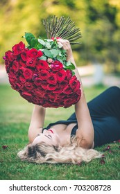 Elegant beautiful blonde woman is wearing black fashion dress lying on green lawn holding with big bouquet of 101 red roses